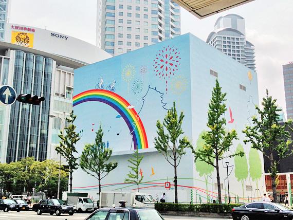 大阪中央郵便局付近の写真。四角い建物があり、水色に塗られた壁には虹の絵が描かれている。