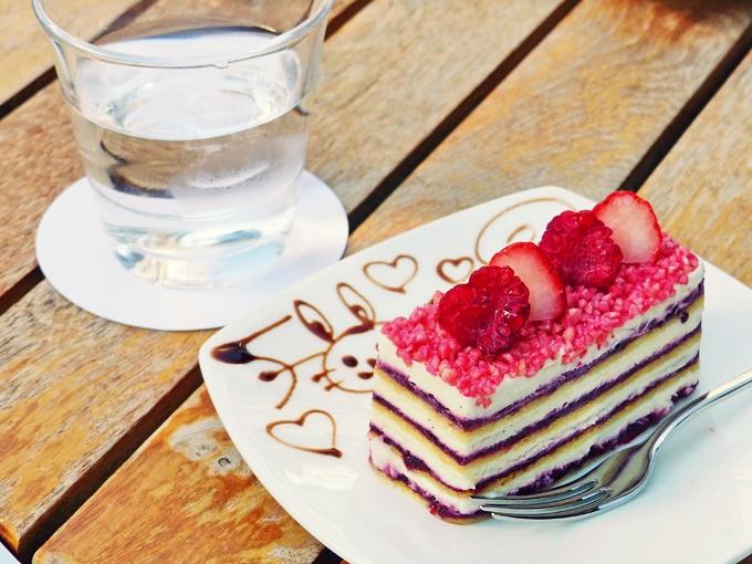 お皿に載ったケーキの写真。スポンジとクリームとベリーのソースが何層にも重なったケーキで、てっぺんにはラズベリーと苺が並べられている。お皿にはチョコレートでかわいい絵が描かれている。