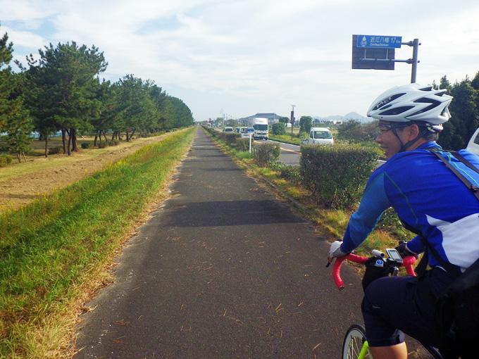 滋賀県野洲市内の湖岸道路の写真。車道とは別に作られた遊歩道がまっすぐに伸びている。