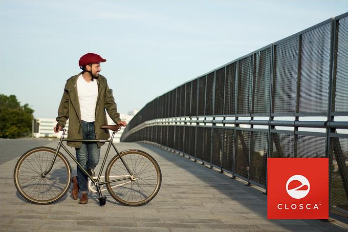 クロスカの赤いヘルメットを被った男性が自転車の横に立って微笑んでいる写真。