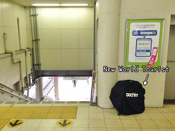 JR守山駅の駅構内に、小さく折り畳まれて輪行袋に収納された状態の自転車「ニューワールドツーリスト」が置かれている。