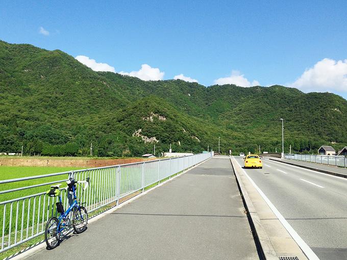 真っ直ぐな道路。この先は橋になっていて、道路は川を越えるようになっている。むこうには山と青空が見える。