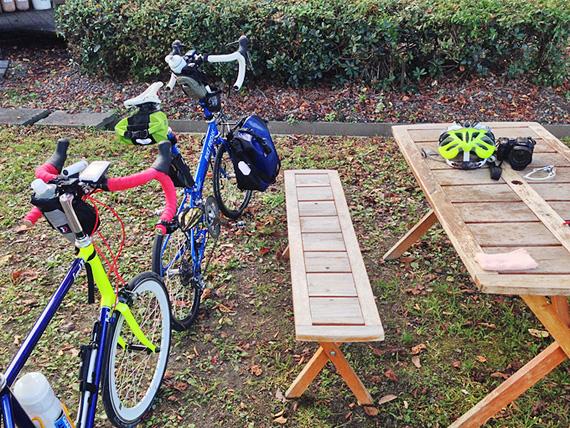 木製のテーブル&椅子の横にバイクフライデーの折り畳みミニベロ「ニューワールドツーリスト」とフジ「コメットR」が停められている写真。