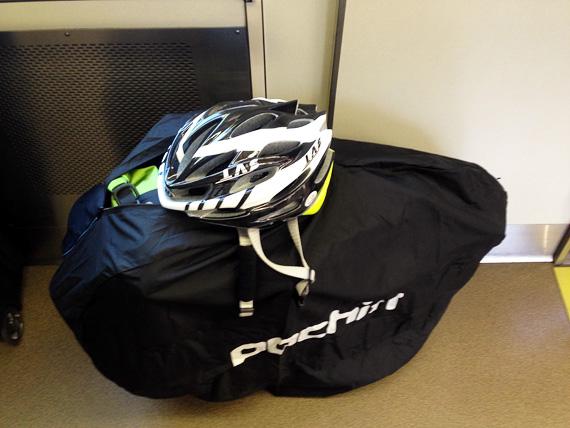 電車の車内の片隅に置かれた黒い袋。中には小さく折り畳まれた自転車「ニューワールドツーリスト」が入っている。袋の上には自転車用のヘルメットが置かれている。