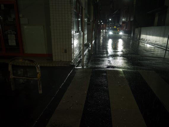 雨が降る、暗い夜道の写真。道路は濡れていて、薄暗い足下にはぼんやりと横断歩道が見える。むこうからライトを点けた車が走ってくるのが見える。