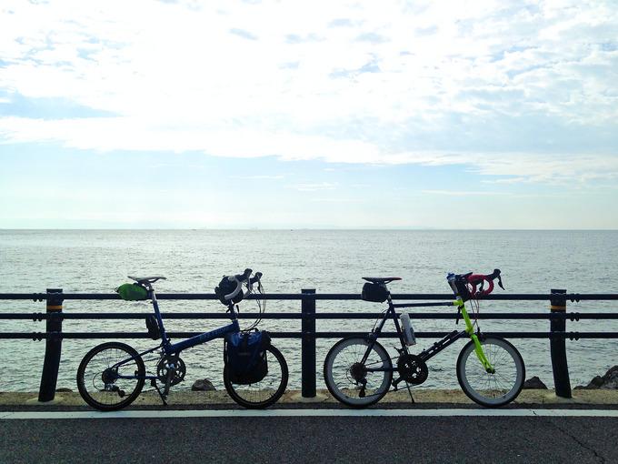 ガードレールの前に2台の自転車、バイクフライデーの折り畳みミニベロ「ニューワールドツーリスト」とミニベロロード「コメットR」が停められている。そのむこうには海が広がっている。