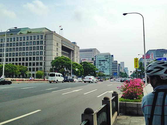 大阪市役所付近の道路の写真。道路は8車線あり、たくさんの車が走っている。むこうに大阪市役所の建物が見える。