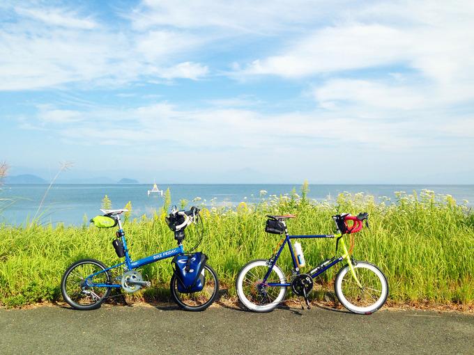 滋賀県高島市新旭の「木津」交差点付近から見る琵琶湖の風景。緑色の草むらのむこうに、青い琵琶湖の水面が広がっている。手前にはバイクフライデーの折り畳みミニベロ「ニューワールドツーリスト」とフジ「コメットR」が停められている。