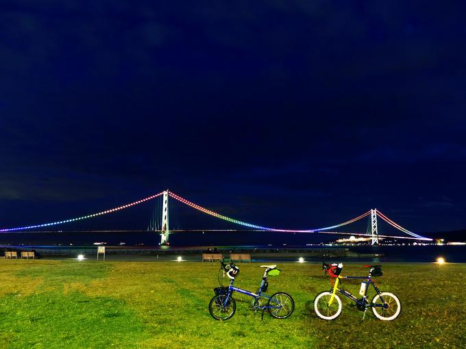 日没後の明石の大蔵海岸公園で見る、明石海峡大橋の写真。電飾が点灯して七色に光っている。手前の広場には2台の自転車、バイクフライデーの折り畳みミニベロ「ニューワールドツーリスト」とミニベロロード「コメットR」が停められている。
