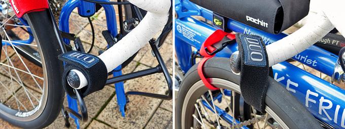 バイクフライデーの折り畳みミニベロ「ニューワールドツーリスト」が折りたたまれた状態で、ハンドルの両端が黒いベルトで固定されている写真。