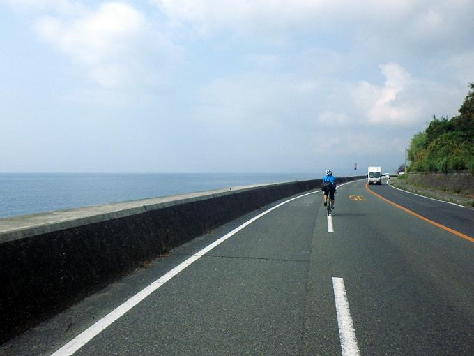海岸線に沿ってゆるやかに曲がっているアスファルトの道を友人が乗った自転車が走ってゆく。左側の壁のすぐむこうには青い海が広がっている。