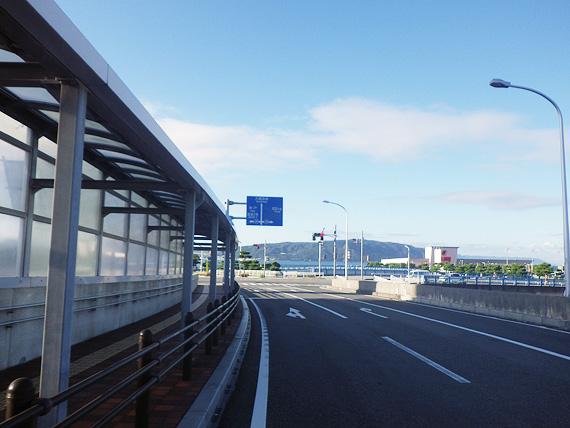 兵庫県明石市の大蔵海岸付近の道路の写真。むこうに明石海峡の海と淡路島が見える。