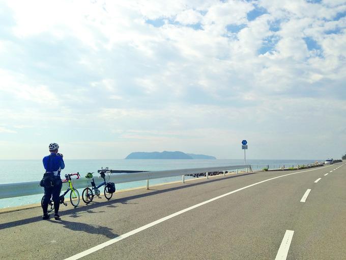淡路島の南部「南淡路水仙ライン」から見る風景。まっすぐに伸びる道と、白いガードレール、そのむこうには青い海が広がっている。海の先には「沼島」が見える。