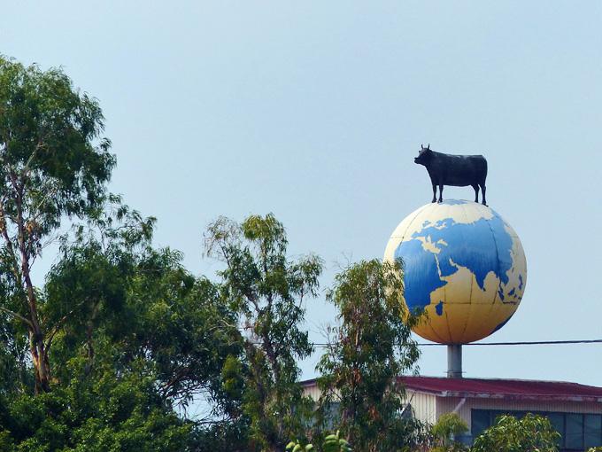 大きな地球儀のようなものの上に黒毛和牛のオブジェが立っている形の看板。