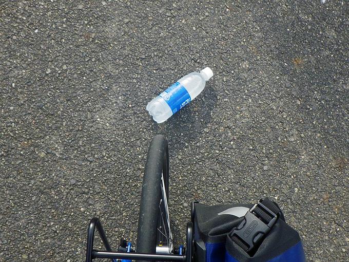 ニューワールドツーリストの前輪の前に「ポカリスエット」のペットボトルが落ちている写真。