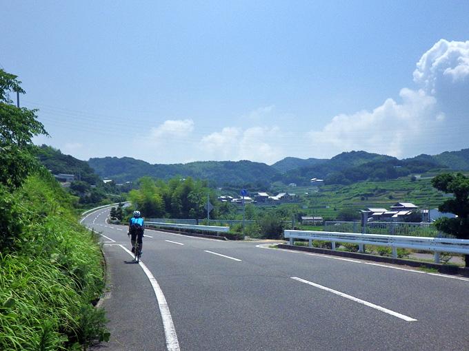 曲がりくねりながら登ってゆくアスファルトの山道を、友人が乗った自転車が登ってゆく。
