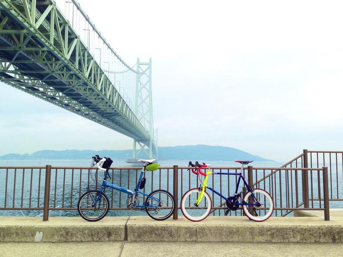 巨大な吊り橋「明石海峡大橋」の真下で、護岸のフェンスに立てかけられた2台の自転車の写真。
