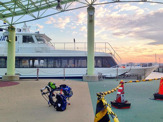 淡路島の岩屋港に到着したジェノバラインの船と、桟橋に置かれた折り畳み自転車「ニューワールドツーリスト」の写真。