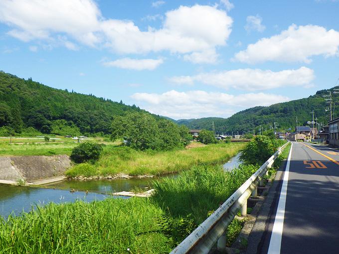 真っ直ぐに続く道路。白いガードレールの向こう側には、川が流れていて、周りには草が生い茂り、むこうには草むらと山が続いている。