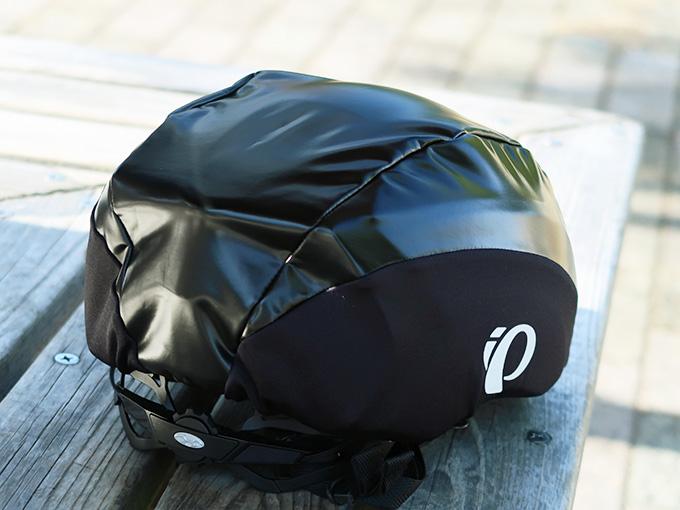 自転車用ヘルメットにヘルメットカバー(パールイズミのレインヘルメットカバー)を装着した写真