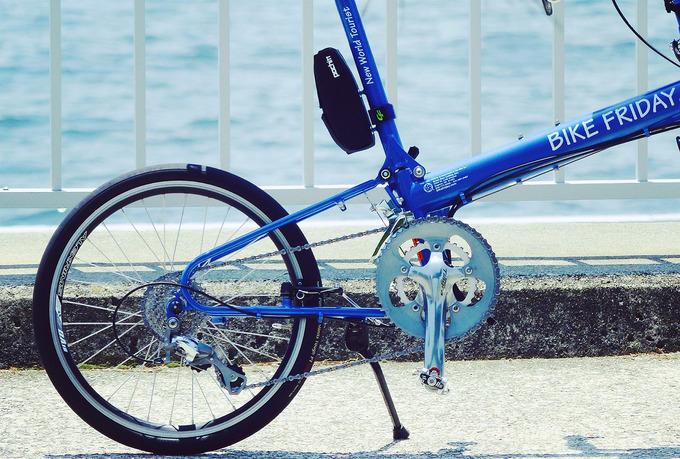 バイクフライデーの自転車「ニューワールドツーリスト」の後ろ半分を写した写真。青いフレームで、銀色の大きなギアが付いている。背景には白いフェンスと青い海が見える。