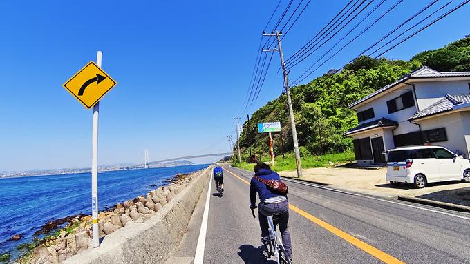 淡路島・松帆の浦付近の風景の写真。左側には青い海が広がり、前方には明石海峡大橋が見える。