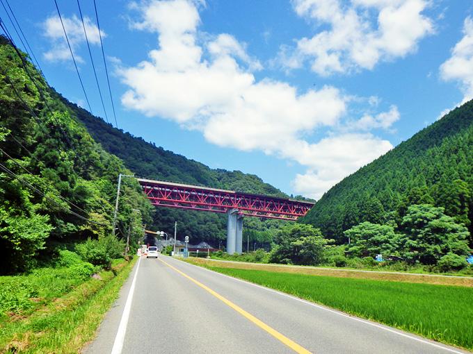 両側を山に挟まれた真っ直ぐな道路。この道路の先には、大きな赤い鉄橋があり、道路の上を横切っている。あの赤い鉄橋は「中国自動車道」だ。