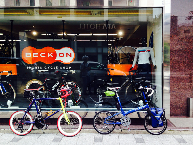 大阪の本町にある自転車屋さん「ベックオン」の店舗入り口付近の写真。ガラス張りのショーウィンドウの中にはロードバイクが展示されている。その前に、2台の自転車「ニューワールドツーリスト」と「コメットR」が停められている。
