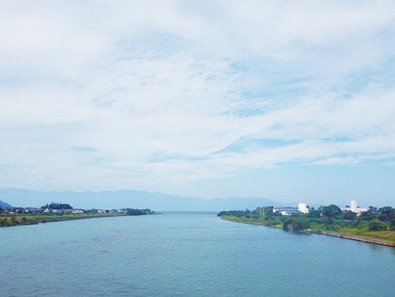滋賀県東近江市を流れる「愛知川」の写真。青い水面が琵琶湖へと続いている。