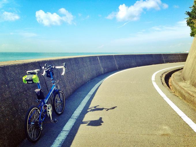 兵庫県明石市内の「播磨サイクリングロード」の写真。右にカーブした道の左側には青い海が広がっている。カーブの外側の壁の横に、バイクフライデーの折り畳みミニベロ「ニューワールドツーリスト」が停められている。