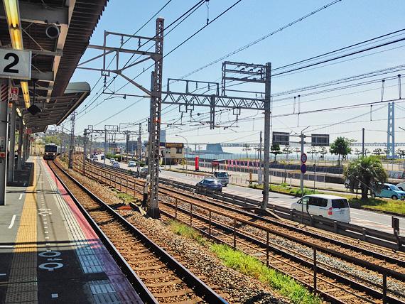 JR朝霧駅のホームから東側を見た写真。右側には海が見え、むこうに明石海峡大橋が見えている。むこうから電車がホームに入ってくるのが見える。