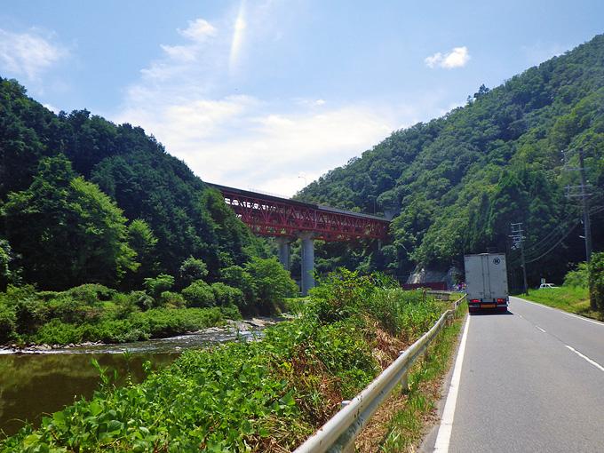 山間をゆく道路、その先にはこの道路を横切る中国自動車道の赤い鉄橋が見える。