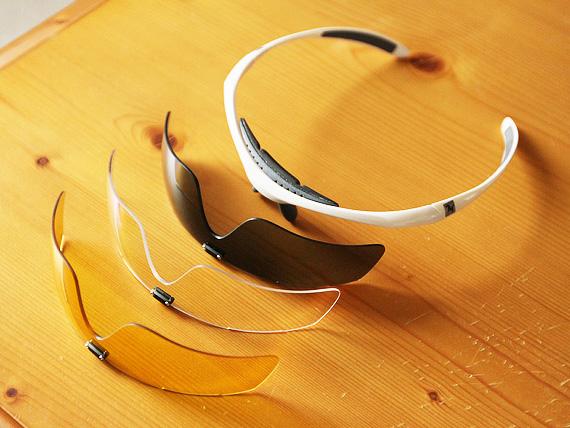 レンズが外された白いサングラスのフレームと、その前に並べられた3つのレンズ。レンズはそれぞれグレー、透明、黄色が外観をしている。