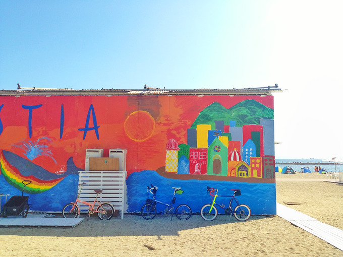 海水浴場の砂浜に建てられた「海の家」の裏側の壁にカラフルなアートがペイントされている。そのカラフルな壁を背景に、折り畳みミニベロ「ニューワールドツーリスト」と、ミニベロロード「コメットR」が停められている写真。地面は砂浜で、建物の向こうには青い海が見える。