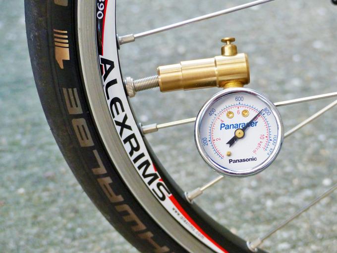 自転車のタイヤの空気圧を計測・調節している写真。バルブに空気圧計が装着されている。