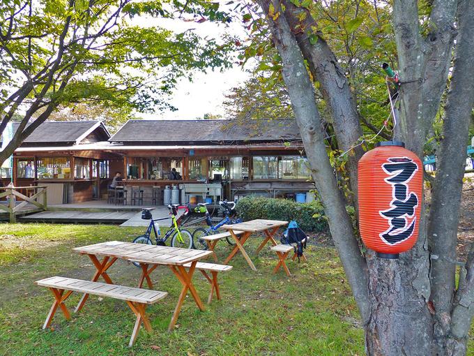 道の駅「しんあさひ風車村」内の「わらべの森・テント村」エリアにある食堂付近の写真。ログハウスのような食堂の建物の前に、木製のテーブル&椅子がある。
