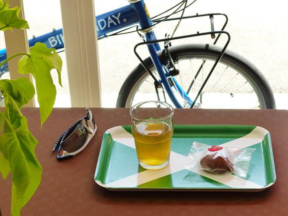 小さなトレーの上に、コップに入った冷たい緑茶と、丸くて茶色い揚げまんじゅうが1つ。手前には観葉植物の緑色の葉、むこうには店先に停められた青い自転車が見える。
