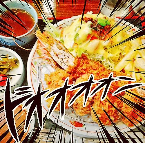 エビフライとヒレカツの定食をクローズアップした躍動感のある写真。「ドォォォン」という文字が付け加えられている。