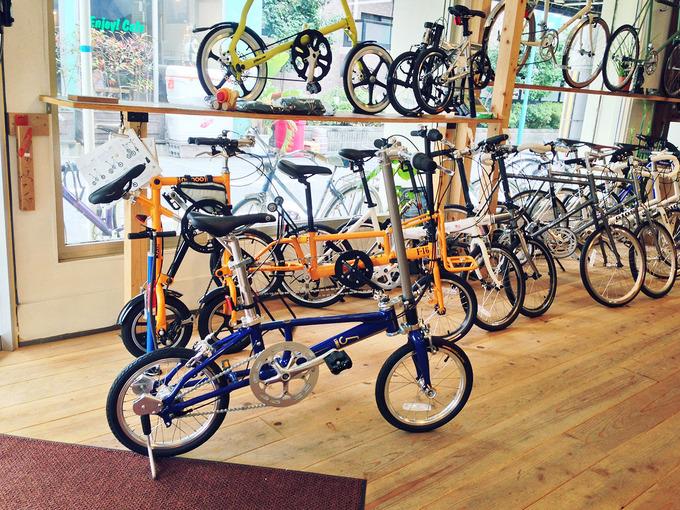 自転車屋さんの店内に色々な種類のミニベロが並んでいる写真。どの自転車もタイヤが小さく、色や形は様々である。