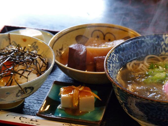 「玉子かけ、そば・うどんセット」の写真。玉子かけめし、汁そばの他に、漬物、おでん、胡麻豆腐が一緒に並べられている。