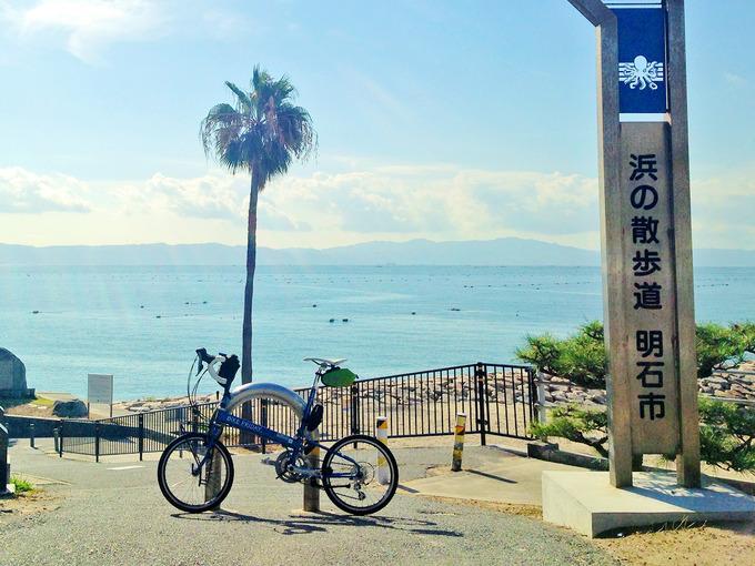 播磨サイクリングロードの江井ヶ島付近の写真。少し高台になっていて、「浜の散歩道・明石市」と書かれた看板がある。むこうには海と椰子の木が見える。手前にはバイクフライデーの折り畳みミニベロ「ニューワールドツーリスト」が停められている。