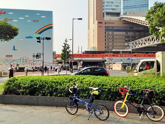 大阪中央郵便局付近の写真。四角い建物があり、水色に塗られた壁には虹の絵が描かれている。むこうには横断歩道があり、その手前に2台の自転車「ニューワールドツーリスト」と「コメットR」が停められている。