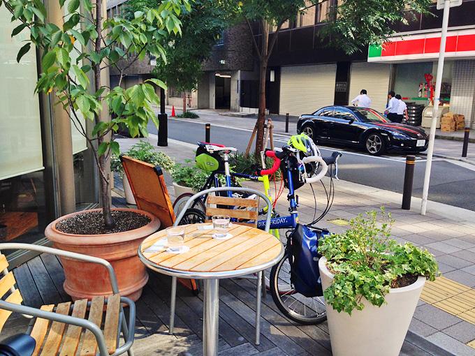 「フォーチェ」のお店の外にあるウッドデッキに、テーブルと椅子が並べられ、その隅にバイクフライデーの折り畳みミニベロ「ニューワールドツーリスト」と、友人のミニベロロード「コメットR」が停められている写真。