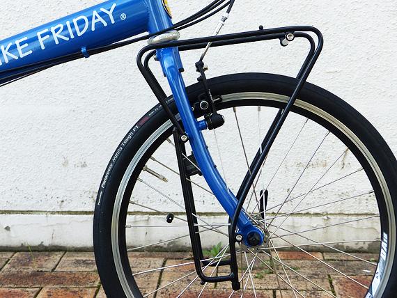 バイクフライデーの折り畳みミニベロ「ニューワールドツーリスト」のフロントフォーク周辺を真横から見た写真。青いフロントフォークの外側には黒いパイプで作られたフロントキャリアが装着されている。