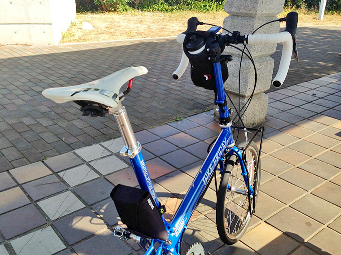 日陰に停められたバイクフライデーの折り畳みミニベロ「ニューワールドツーリスト」を斜め後ろから見た写真。サドルの位置調整をするために、サドルバッグが取り外されている。