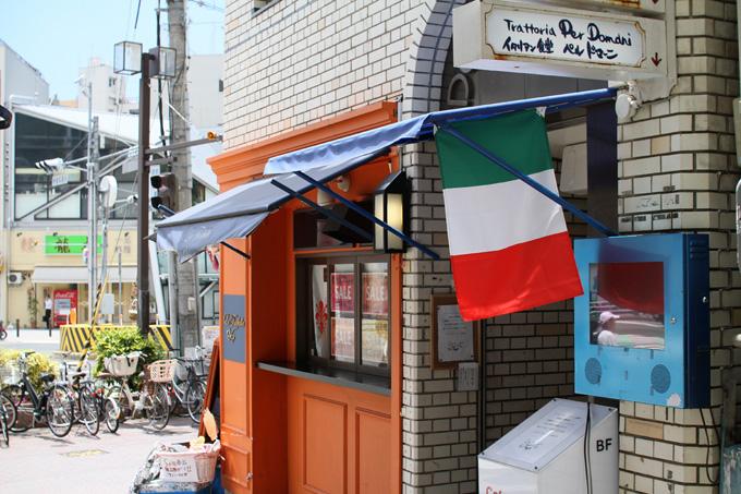 信号のある交差点に面したビルの1階部分の壁に、地下へと降りる階段の入り口がある。その上にはイタリア国旗が掲げられていて、「イタリアン食堂・ペルドマーニ」とお店の名前が書かれた看板がある。