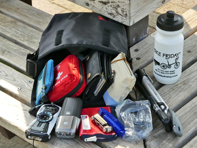 フロントバッグ「シースリーショルダーS」を自転車から取り外して、バッグの中身を取り出して並べている写真。色々なものが収納されていたことがわかる。
