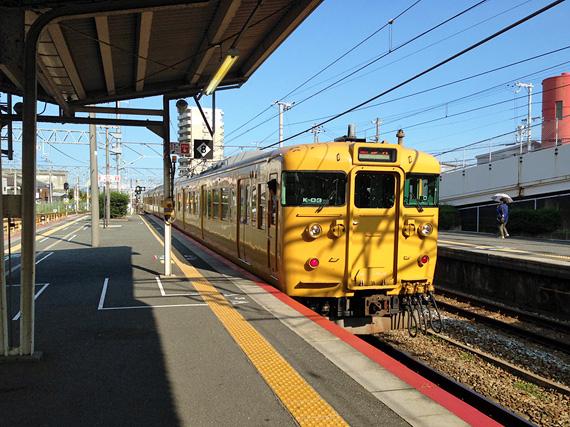 駅のホームから出てゆく、とても古そうな黄色い電車。