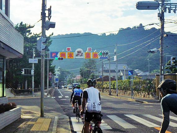 淡路島・洲本温泉街付近の写真。アーチ状の看板があり、「歓迎・洲本温泉」と書かれている。その下を何台ものロードバイクが走り抜けてゆく。