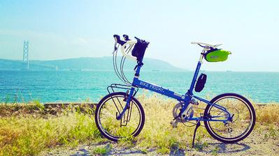 すっきりと晴れた青空に、マリンブルーの海、むこうには淡路島が見える。そんな場所を背景に、鮮やかな青いフレームの折り畳みミニベロ「バイクフライデーのニューワールドツーリスト」を写した写真。